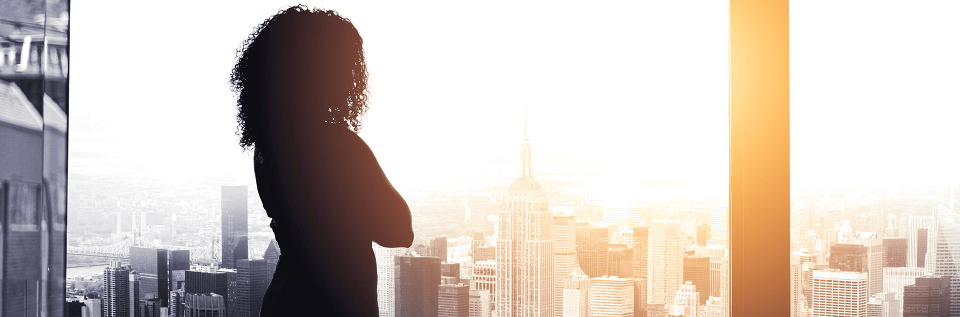 Business woman looking out window at New York City
