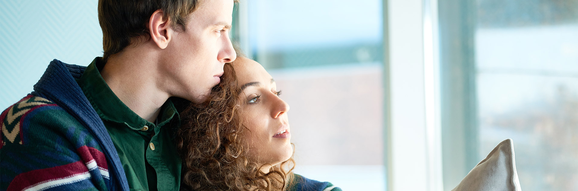couple in serious thought looking out a window