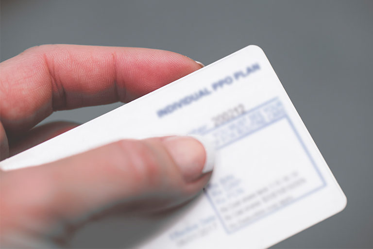hand holding insurance card